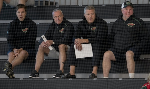 Wild assistant coach Darby Hendrickson (left, with assistants Dean Evason and Bob Woods and head coach Bruce Boudreau) tries to help players during ga