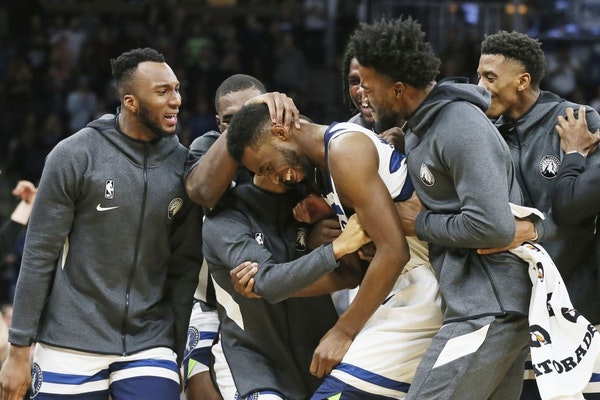 Andrew Wiggins (22) is swarmed by teammates after his third straight 3-pointer against the Miami Heat in the second half on Sunday night.