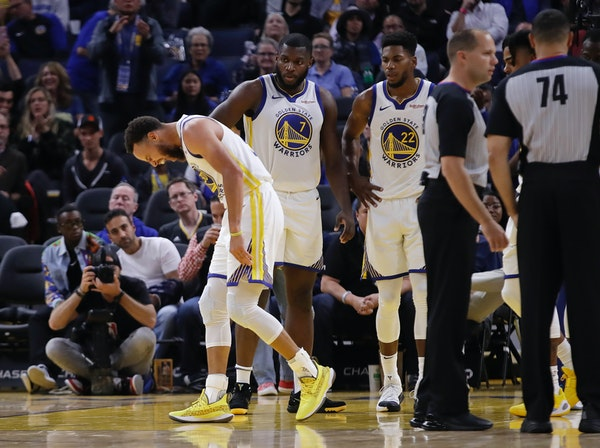Golden State Warriors' Stephen Curry, left, grimaces after Phoenix Suns' Aron Baynes fell onto him during the second half.