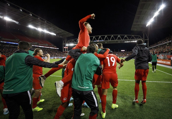 Canada midfielder Scott Arfield, top, and teammates celebrate a goal by forward Lucas Cavallini (19) in a CONCACAF Nations League soccer match against