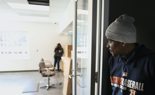 Antonio Kelly peeked into a salon where residents can get haircuts at Dorothy Day Place, where Kelly has an apartment after three years with no home.