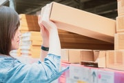 woman shopping and job concept from beauty asian girl in blue jean shopping and hold big box in hardware store for support her construction job