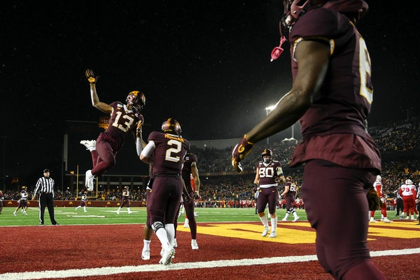 Gophers wide receiver Rashod Bateman (13) and quarterback Tanner Morgan (2) rushed to join a celebration with running back Mohamed Ibrahim after he sc