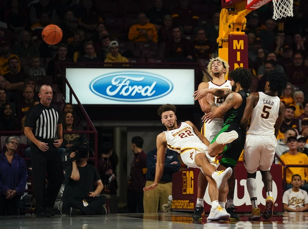 North Dakota guard Marlon Stewart (1) plowed into Minnesota's Gabe Kalscheur (22), Jarvis Omersa (21) and Marcus Carr (5) on Sunday during the first h