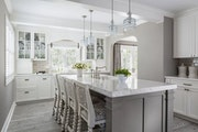 The white quartz-topped island for casual dining feels fresh and distinctive, thanks to the chunky chiseled edge on the counters and island top.