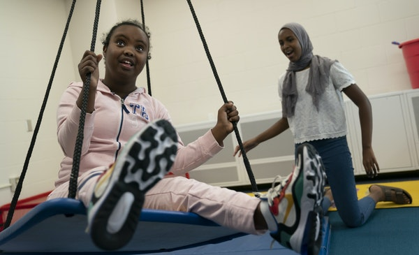 Peer Insights student Muna Mohamud-Karie, 13, right, gave Hanan Sharif a push on a swing at South View Middle School in Edina.