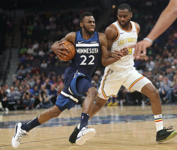 Andrew Wiggins drives to the basket while covered by Golden State's Alec Burks