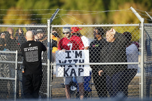 Fans watched from behind a fence as free agent quarterback Colin Kaepernick participated in a workout Saturday in Riverdale, Ga.