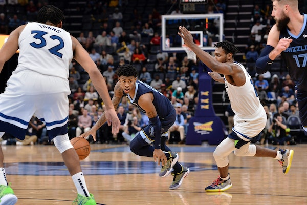Memphis guard Ja Morant handles the ball between Timberwolves forward Treveon Graham, right, and center Karl-Anthony Towns