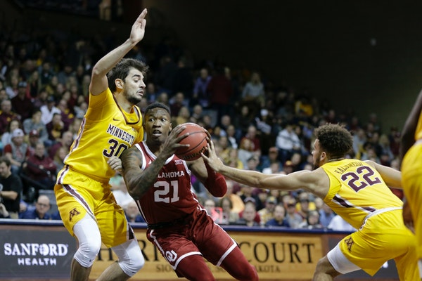 Oklahoma's Kristian Doolittle goes to the basket between Minnesota's Alihan Demir (30) and Gabe Kalscheur (22) during the first half.