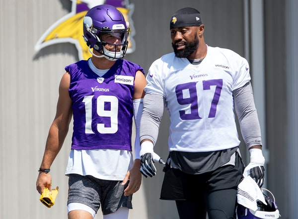 Vikings wide receiver Adam Thielen (19) and defensive end Everson Griffen talked while they walked out for an afternoon practice.