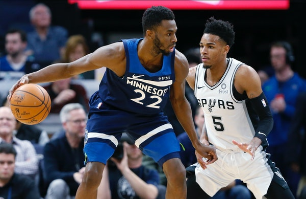 The Timberwolves' Andrew Wiggins, left, drives around San Antonio Spurs' Dejounte Murray in the first half.
