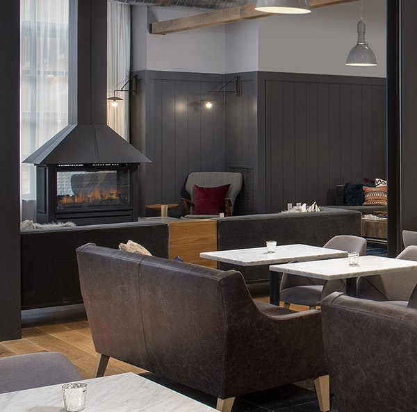 A fireplace anchors the lobby and restaurant at Canopy Ithaca.
