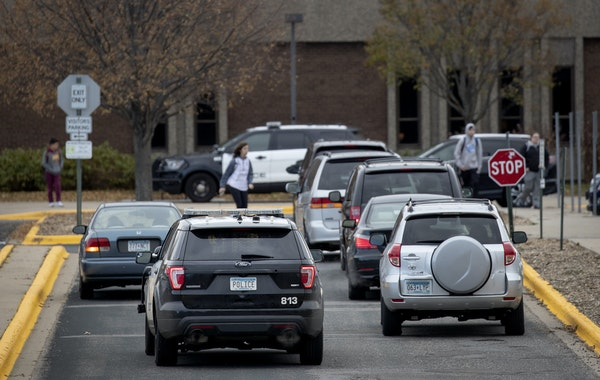 A police vehicle pulled up to Bloomington Jefferson High School while cars waited to pick students. (Carlos Gonzalez/Minneapolis Star Tribune/TNS) ORG