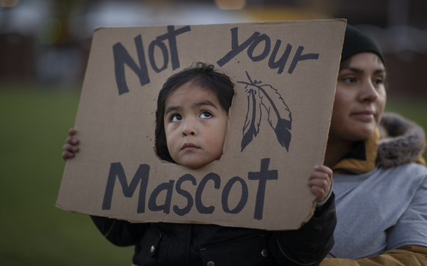 Fox Iron Eaglefeather 3, with mother Melody Iron Eaglefeather, protested the nickname and mascot of the Washington NFL team at the Commons in Minneapo