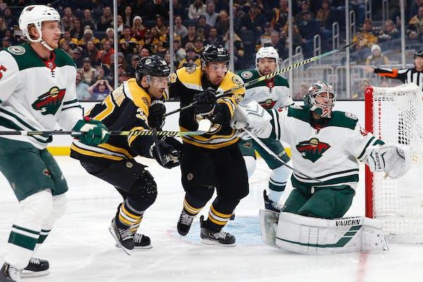 Boston's Patrice Bergeron (37) and Brad Marchand (63) chase a deflection off Wild goalie Alex Stalock