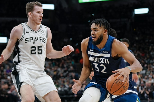The Timberwolves' Karl-Anthony Towns drives against San Antonio Spurs' Jakob Poeltl during the first half