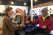 """Great Lakes Gear Exchange co-owner Brooke Wetmore rang up a ski jacket for Joe Schiavone. """"I couldn't pass it up. It's a great deal,"""" he said."""