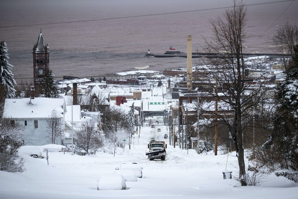 A snowplow worked to clear streets in Duluth Sunday morning. But days later, some areas of the city remain impassable.