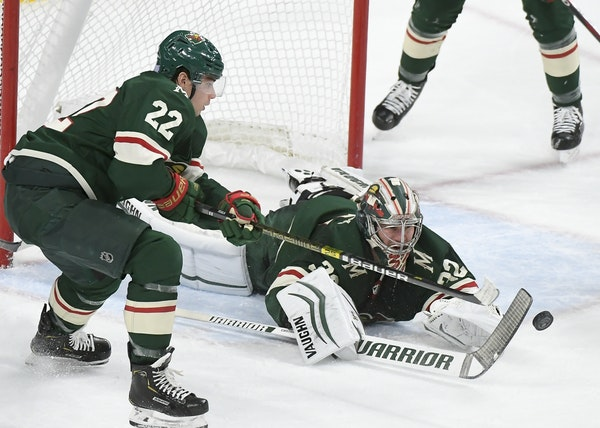 Minnesota Wild goaltender Alex Stalock (32) leapt forward for a save with the help of left wing Kevin Fiala (22) in the second period.