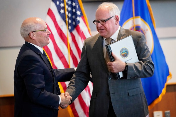 Gov. Tim Walz, right, and Myron Frans, of Management and Budget, had a reason to smile.