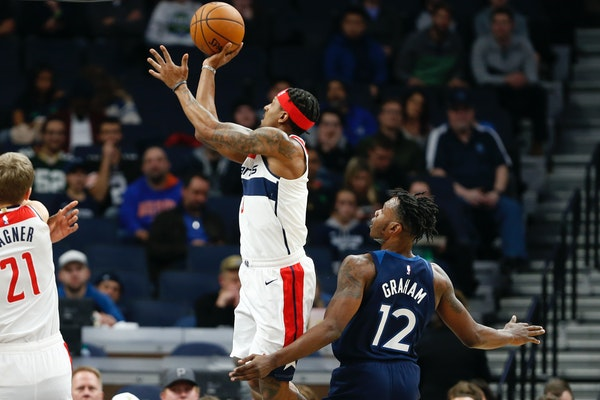 Bradley Beal, center, shoots as the Timberwolves' Treveon Graham looks on in the first half