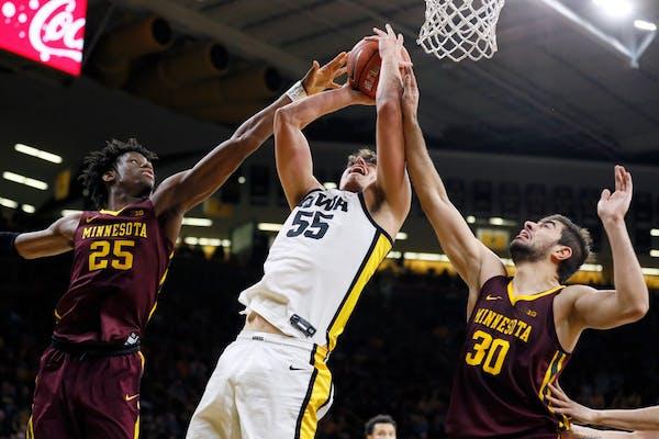 Iowa center Luka Garza, center, drives to the basket between Minnesota's Daniel Oturu, left, and Alihan Demir, right, during the second half