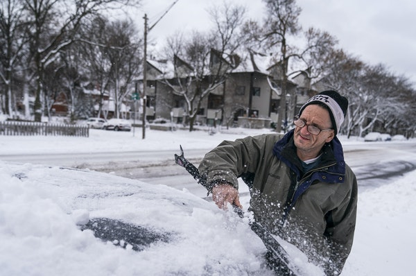 """Patrick Costanzo of St. Paul brushed snow off a friend's car on Selby Avenue in St. Paul. """"I'm used to it,"""" Costanzo said of the snow. """"You"""
