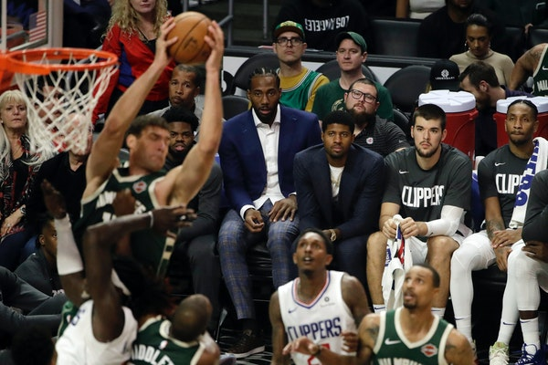 Kawhi Leonard, center, and Paul George, third from right, watch from the bench during the second half of the team's game against the Milwaukee Bucks o