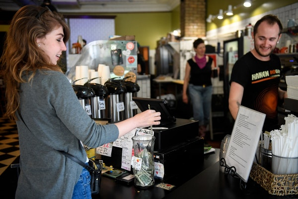 Barista Andy Regan, right, watched as Jennifer Ivers, of Minneapolis, placed a dollar in the tip jar Wednesday afternoon at Maeve's Cafe. ] AARON LA