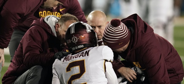 Football coach P.J. Fleck and Gophers trainers attended to quarterback Tanner Morgan (2) after a hard sack in the fourth quarter in Saturday's 23-19 l