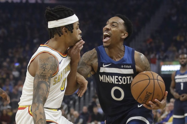 Minnesota Timberwolves guard Jeff Teague, right, drives to the basket as Golden State Warriors guard D'Angelo Russell defends during the first half of