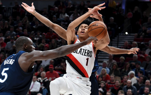 Minnesota Timberwolves center Gorgui Dieng, left, knocks the ball away from Portland Trail Blazers guard Anfernee Simons during the second half of an
