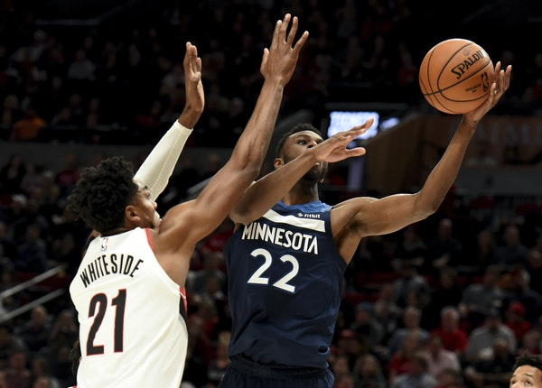 Minnesota Timberwolves forward Andrew Wiggins, right, drives to the basket on Portland Trail Blazers center Hassan Whiteside during the first quarter