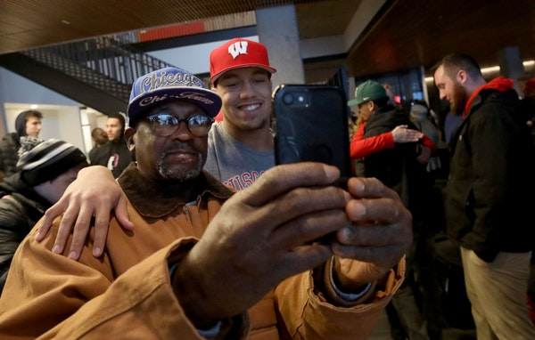 Minnehaha Academy football products Kaden Johnson takes a photo with his grandfather,Jimmy Johnson, during a national signing day ceremony.