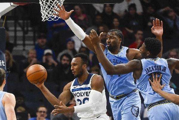 Wolves guard Josh Okogie passed the ball under the basket while being guarded by Grizzlies forward Solomon Hill, center, and forward Jaren Jackson Jr.