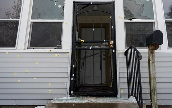 Bullet holes marked the front of the house on N. Thomas Avenue in Minneapolis, the scene of an officer-involved shooting Sunday that killed a man.