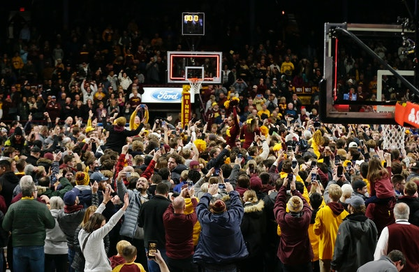 Minnesota fans storm the court after an upset victory over Ohio State