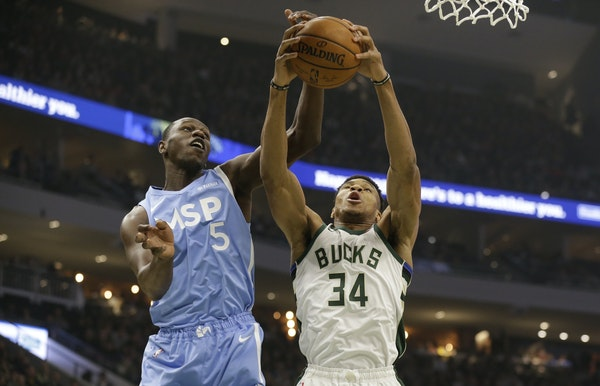 The Bucks' Giannis Antetokounmpo (34) fought for a rebound against Timberwolves center Gorgui Dieng during the first half Wednesday. Antetokounmpo h