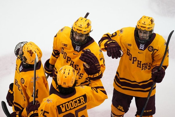 Gophers forward Blake McLaughlin (27) was congratulated by his teammates after he scored the game-winning goal against Bemidji State on Saturday night