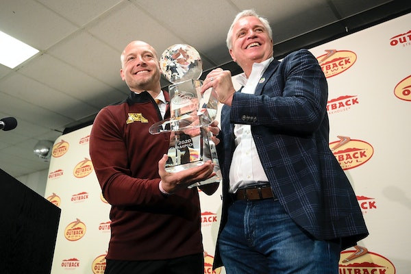 Gophers coach PJ Fleck posed for photos with the Outback Bowl trophy alongside Blooming Brand CEO David Deno.