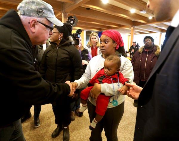 Minnesota Gov. Tim Walz, left, and Minneapolis Mayor Jacob Frey, right, met with displaced Francis Drake Hotel residents at Bethlehem Baptist Church,