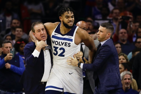 Wolves assistant coach Bryan Gates, left, tried with coach Ryan Saunders to get Karl-Anthony Towns off the floor following Towns' altercation with P