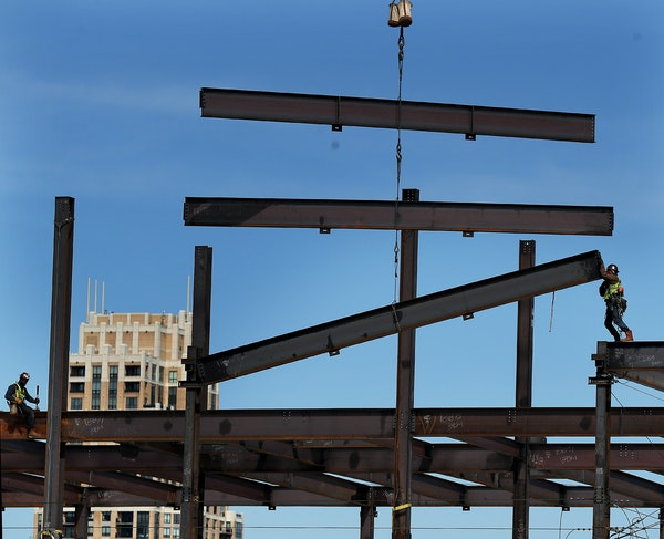 A construction worker, with the help of a crane, guides steel beams into place on the new Thrivent Financial building April 3, 2019, in Minneapolis. O