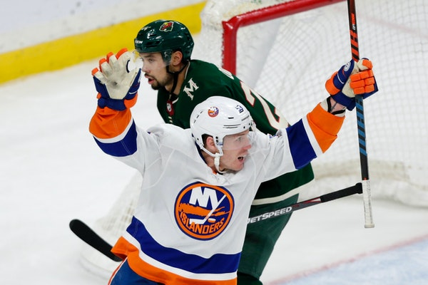 New York Islanders' Casey Cizikas celebrates a goal as Wild defenseman Matt Dumba skates away in the third period