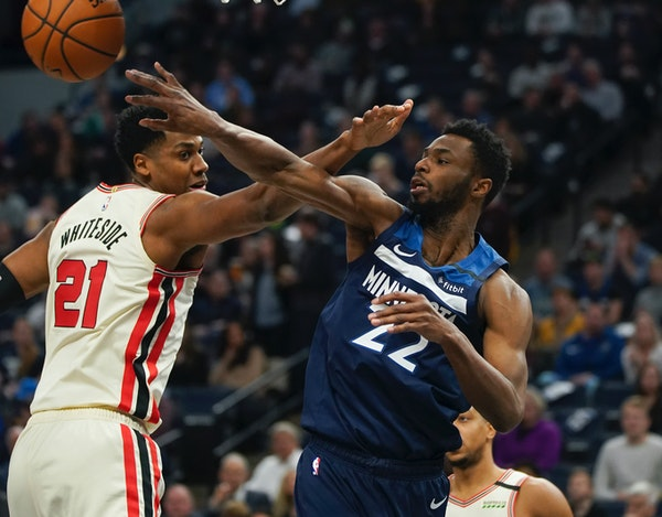 Timberwolves forward Andrew Wiggins passed off to a teammate around Trail Blazers center Hassan Whiteside in the second quarter.