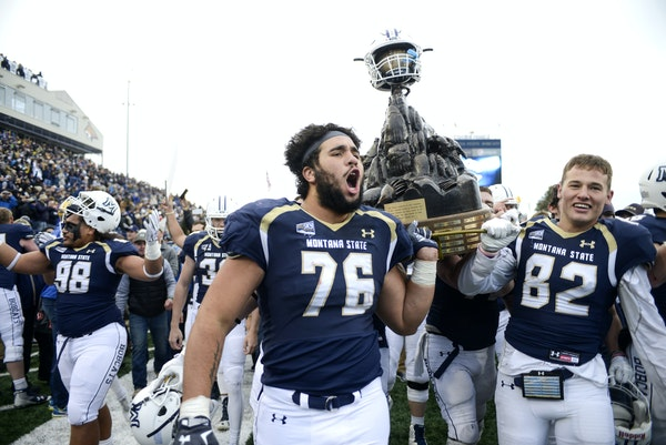 Montana State offensive lineman Lewis Kidd (76) and wide receiver Mitchell Herbert helped carry the Great Divide Trophy after a 31-20 victory over riv