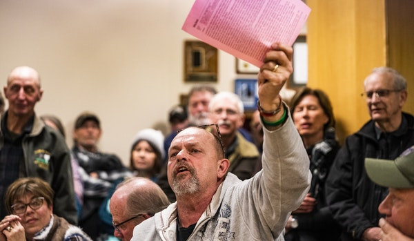 """""""For me it was always about financial stability,"""" says Mike Rasch, who says the county cannot afford to welcome refugees. He held up copies of his com"""