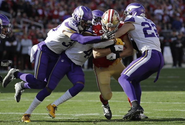 San Francisco 49ers tight end George Kittle, center, is tackled by Minnesota Vikings Minnesota Vikings free safety Harrison Smith, right, and other de