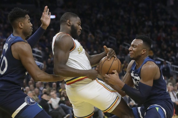 Minnesota Timberwolves guard Josh Okogie, right, takes the ball from Golden State Warriors forward Eric Paschall, center, during the second half of an